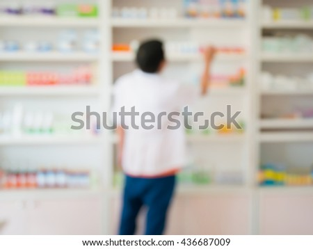 blur image of pharmacist working in the pharmacy - stock photo