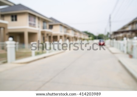 blur image of road with a car and house in the village.