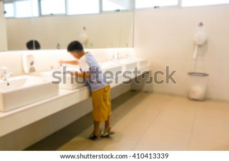 Blur image of the boy washing his hand in the sink ,use for background. - stock photo