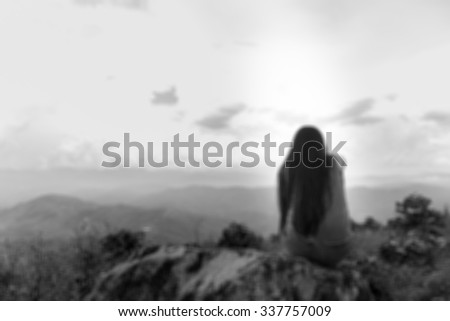 blur image: Young women siting alone on a rock,Sad concept-blur background