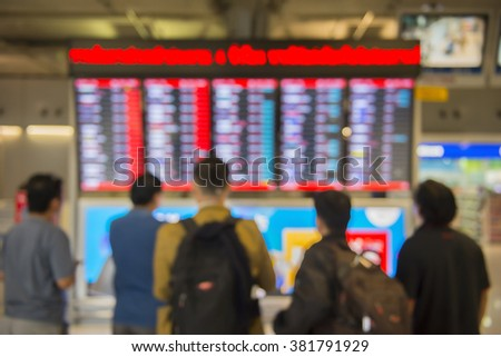 Blur motion abstract of An Airport Departures monitor showing flight times flight status and destinations with passenger. - stock photo