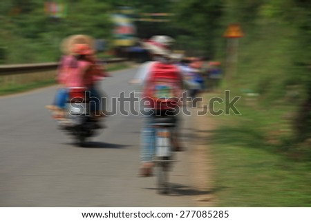 Blur motion of a schoolgirl cycling to school - stock photo