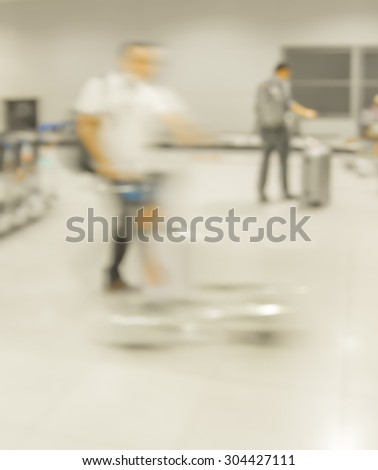 blur motion of walking people and trolley in airport - stock photo
