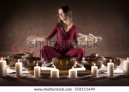 Blur motion photo of a woman playing a Tibetan bowls, focus on a singing bowls - stock photo