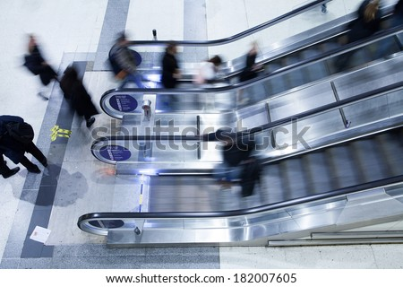 Blur Movement Business people walking on escalator in Rush Hour train station, London, UK  - stock photo