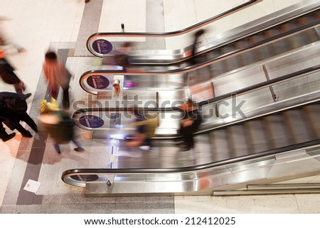 Blur Movement Business people walking on escalator in Rush Hour train station, London, UK  - stock photo