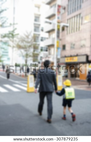 Blur of Dad and Son walking on street - stock photo