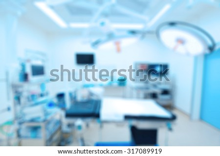 Blur of equipment and medical devices in modern operating room take with art lighting and blue filter