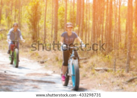 Blur of girl on bikes cycling outdoors, active girl sport,forest