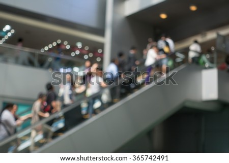blur of people that using escalator at shopping mall - stock photo