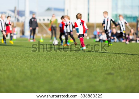 Blur of young kids playing a soccer training match outdoors on an artificial soccer pitch. - stock photo