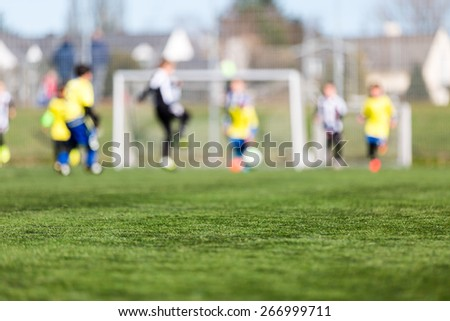 Blur of young kids playing a youth soccer match outdoors on an green soccer pitch. - stock photo