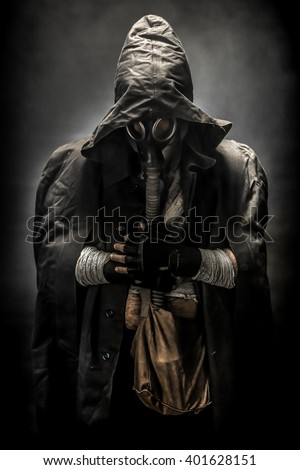 blur or defocus image of a man in the gas mask in the hood, on the black background surrounded by smoke, with hands on the chest, survival soldier after apocalypse. - stock photo