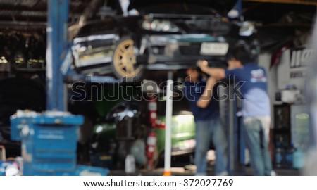 Blur or Defocus image of Mechanic working in auto repair garage. Car maintenance. - stock photo