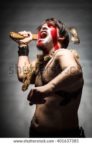 blur or defocus image of portrait of man in war paint, with an ax in his hand, a warrior brandishing an ax up furiously screaming, barbarian of ancient times, Viking and savage.