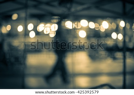 blur shadow of man walking in street in front of shop, market or coffee shop with bokeh light, effect by vintage style, vintage image, vintage tone - stock photo