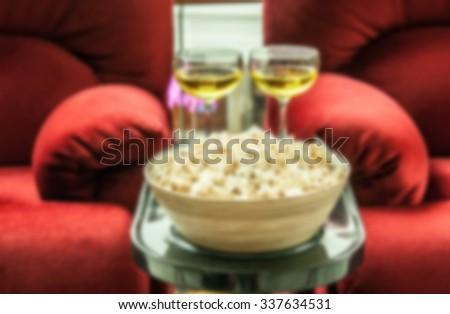 blur shot of popcorn and drink on cinema seat - stock photo