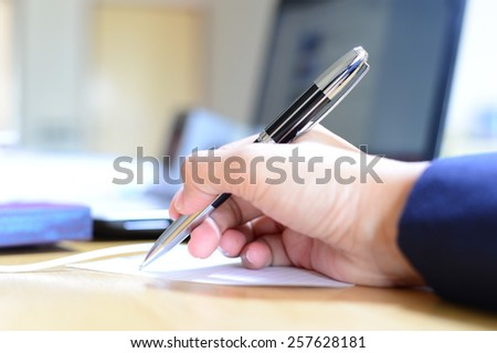 blur sign pen in business woman hand on computer notebook background - stock photo