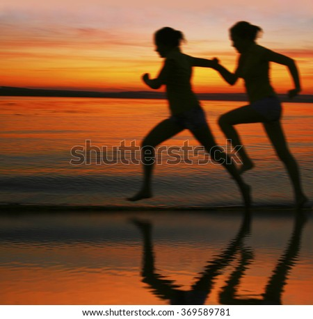 blur silhouette of two women running at sunset or sunrise Girl move along sun set sunny beach Reflection light on water texture lesbian Couple Doing sports exercises against sky with clouds - stock photo