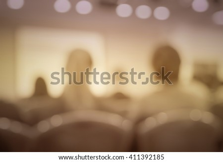Blur vintage  image style of audience in classroom or auditorium with screen, brown color - stock photo