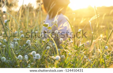 Blur woman sitting in a field grass in the evening.