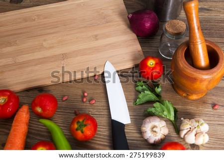 Blured background with green and vegetables, onion, tomatoes, garlic and knife on table