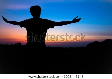 Blurr. Silhouette,Asian young man in hat hiking standing open arm happy at mountain peak above sunset ligth, Hiker outdoor.