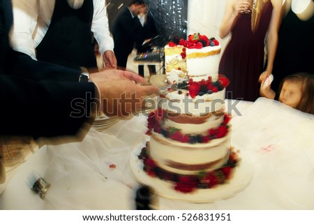 Blurrd picture of newlyweds cutting perfect white wedding cake with berries