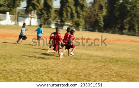 Blurred a group of elementary children racing in green field. - stock photo