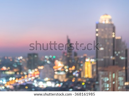 Blurred abstract background aerial view of Bangkok cbd downtown faded night lights colorful bokeh in warm vintage retro golden color tone: Central business district on electric train line over river  - stock photo
