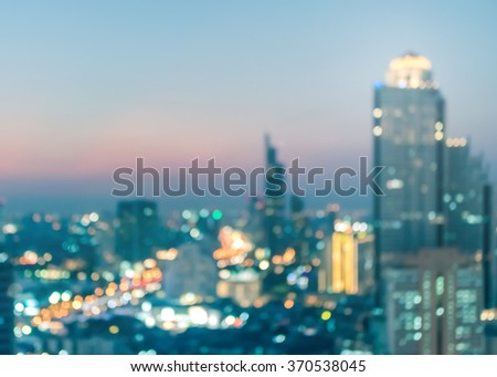 Blurred abstract background aerial view of Bangkok cbd downtown night lights colorful bokeh in cool vintage cyan turquoise blue color tone: Central business district on electric train line over river - stock photo