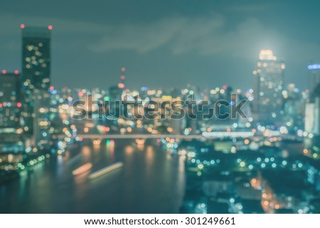 Blurred abstract background aerial view of Bangkok downtown city lights with colorful bokeh in cool vintage cyan turquoise blue color tone with film effects : Central business district at night  - stock photo