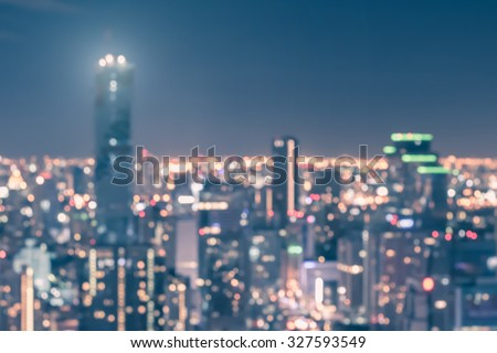Blurred abstract background aerial view of Bangkok downtown city night lights with colorful bokeh in cool vintage pastel cyan blue tone: Central business district cbd on rooftop scenic panoramic view - stock photo