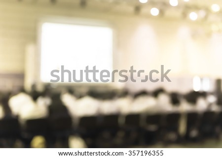Blurred abstract background business/ educational conference and presentation in auditorium hall. Blurry perspective view of people/ student audiences sitting in seat rows in large conference room - stock photo