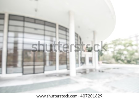 Blurred abstract background exterior view looking toward to empty office lobby and entrance doors and glass curtain wall with frame: Blurry perspective of reception hall to building interior entrance - stock photo