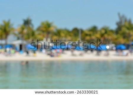 Blurred abstract background image of ocean beach with umbrellas and palm trees. - stock photo
