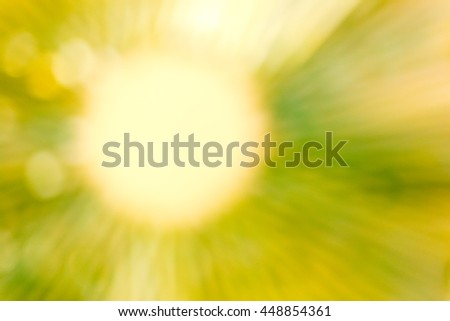 Blurred abstract background in greenish yellow tone, soft yellow circle with soft straight lines of greenish yellow light radiate outward - stock photo