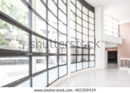 Blurred abstract background interior view looking out toward to empty office lobby and entrance doors/ glass curtain wall with frame: Blurry perspective of reception hall to public building entrance - stock photo
