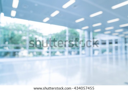Blurred abstract background interior view looking out toward to empty office lobby and entrance doors and glass curtain wall with frame - blue white balance processing style - stock photo