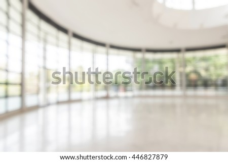 Blurred abstract background interior view looking out toward to empty office lobby entrance doors glass curtain wall frame: Blurry perspective of reception hall to medical center building entry/ exit - stock photo