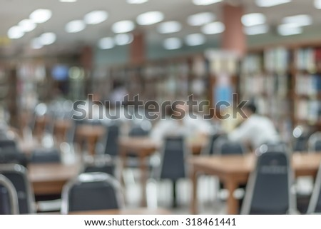 Blurred abstract background of a view school library with of aisles of book shelves and seats for reading: Blurry interior perspective of a study room with tables, chairs and stacks of books     - stock photo