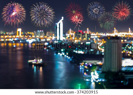 Blurred abstract background of aerial view of Bangkok city night light at Chao Phaya riverfront and bridge across the river with colorful firework, bokeh and light  : Blurry central business district. - stock photo