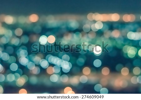 Blurred abstract background of bokeh lights city night shots from bird eye view in vintage color tone : Vintage color tone blurry colorful bokeh lights of night cityscape  - stock photo