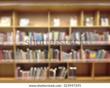 Blurred abstract background of book shelves in public library: Blurry perspective view of a study room with rows and stacks of books: Blur educational interior reading room with textbook - stock photo