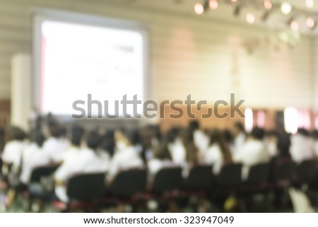 Blurred abstract background of business/ educational conference and seminar in auditorium hall with audiences/ students sitting in seat rows and presenters on stage with projector screen presentation  - stock photo