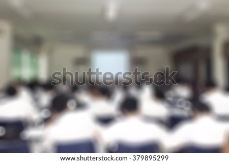 Blurred abstract background of college students sitting in seating rows attending school course: Blurry view from back of the classroom toward projector screen presentation in front of the class room - stock photo