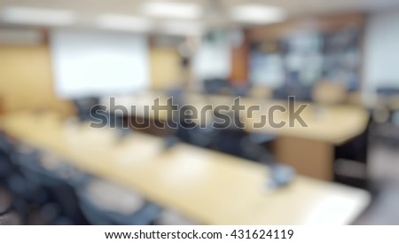 Blurred abstract background of empty projector board in conference room, meeting room. Blurry view of nobody in boardroom, Classroom, Office with chairs and tables with microphone set. - stock photo