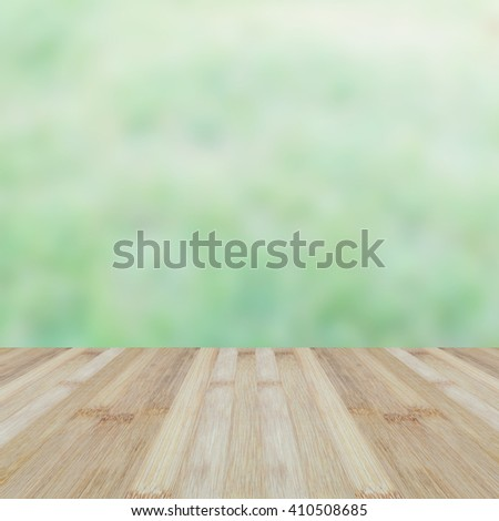 Blurred abstract background of fresh lawn and wooden bamboo floor.Blurry view of green grass with wood table. - stock photo