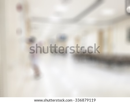 Blurred abstract background of indoor hospital interior in hallway/ corridor/ lobby waiting area for patients, nurse, doctors and clinical staff circulation in clean, bright and hygienic environment  - stock photo