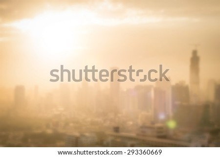 Blurred abstract background of morning gold light view over cityscape cbd downtown Bangkok with bright sun flare and bokeh in warm color tone: Blurry holiday travel backgrounds of urban smokey sunrise - stock photo